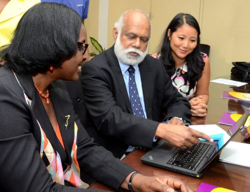 Jamaica Library Service (JLS) Director General, Karen Barton (left), and Microsoft Jamaica's Sector Manager for Education, Queenie Ko (right), observe as the entity's Country Manager, George Gobin, demonstrates features of the Microsoft Office 2013 Pro Plus computer software applications, which were donated by the technology solutions entity, during a presentation ceremony at the JLS' head office, Tom Redcam Drive, St. Andrew, on Friday (June 19). The overall donation is valued approximately $131.85 million (US$1.13 million)