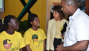 State Minister in the Ministry of Science, Technology, Energy and Mining, Hon. Julian Robinson (right), and President of Jamaica Promotions Corporation (JAMPRO), Diane Edwards (2nd right), converse with graduates of the Jamaican Girls Coding 2014 Summer Camp, Nastacia Virgo (left), and Nastassia Walters, during a graduation ceremony for the programme held on August 22 at the JAMPRO headquarters in New Kingston.