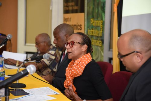 General Manager, Caribbean Country Department, Inter-American Development Bank (IDB), Therese Turner-Jones (second right), addresses public forum at the University of the West Indies (UWI), staged by its Department of Economics and the Planning Institute of Jamaica (PIOJ) on April 12. Listening (from right) are Head, Department of Economics, UWI, Professor David Tennant (right); Director General, PIOJ, Dr. Wayne Henry; and Senior Lecturer, Department of Economics, UWI, Professor Claremont Kirton.