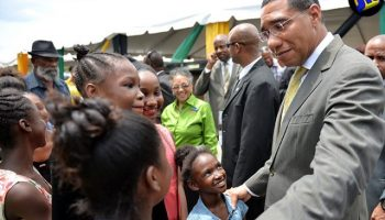 Prime Minister, the Most Hon. Andrew Holness, interacts with children, following a ceremony by the Land Administration and Management Programme (LAMP) to hand over some 220 land titles at Jamaica House, on August 23.