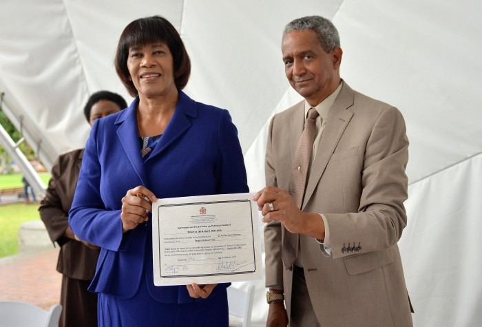 Prime Minister Portia Simpson Miller (left) and Acting Customs of St. Andrew, Lt. Commander John McFarlane show the Political Code of Conduct which the Prime Minister signed signaling her commitment to a peaceful election campaign. The signing took place at Emancipation Park in New Kingston, St. Andrew on Thursday morning (February 11). In the background is Political Ombudsman, Mrs. Donna Parchment Brown.