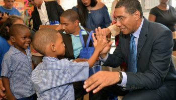 Prime Minister, the Most Hon. Andrew Holness (right), interacts with students at the Four Campbell's Academy, on Booby Drive, in his West Central St. Andrew Constituency,on September 27. Mr. Holness presented books and other educational materials to the school, donated by the Palmyra Foundation.