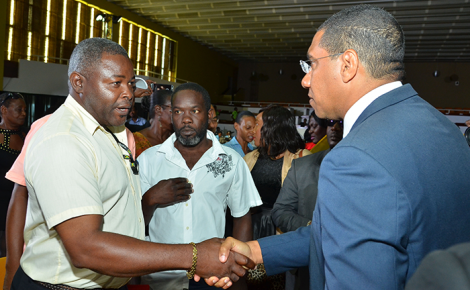 Prime Minister, the Most Hon. Andrew Holness (right), is greeted by Steven Whynn, community participant in the National Housing Trust (NHT) Best Schemes competition 2016/17, following its launch on September 16 at the Jamaica Conference Centre. At second left is another community participant, Raymond Lenard.
