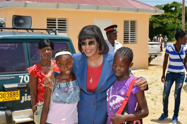 Prime Minister, the Most Hon. Portia Simpson Miller, with two delighted students, Glenoiya Jones (left), of St. Paul's Primary School and Deneisha Thomas of Grange Hill Primary School, both in Westmoreland.  Occasion was the official handing over ceremony for 45 new houses in the Ministry of Agriculture and Fisheries' Sugar Transformation Unit Barracks Relocation Project, at Shrewsbury, in Westmoreland on June 26.