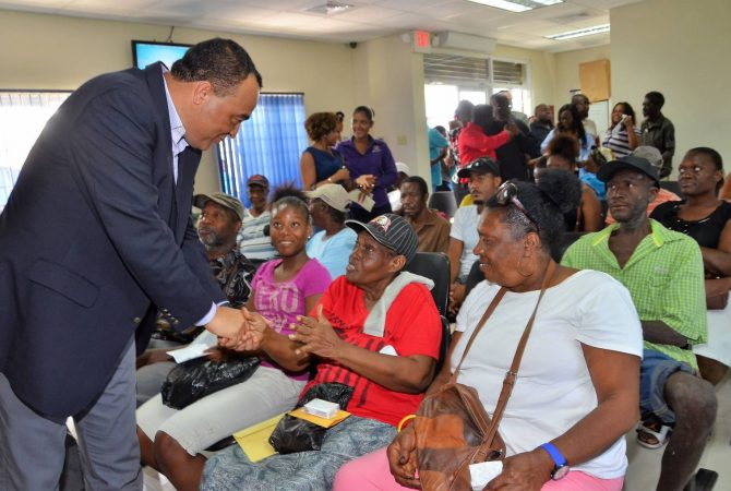 Minister of Health, Hon. Dr. Christopher Tufton (left), greets patients at the upgraded Drug Serv Pharmacy in Greater Portmore, St. Catherine, which was officially opened on Friday (June 9). The improvement work was undertaken at a cost of $42 million.