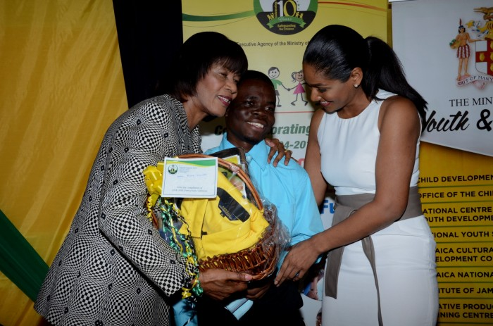 Prime Minister, the Most Hon. Portia Simpson Miller (left), embraces medical student at the University of the West Indies, Mona, McKoy McNish (centre), as he presents her with a gift basket on behalf of the Child Development Agency (CDA), during the 3rd annual Educational Achievement Awards Ceremony for wards of the State, held at the Terra Nova Hotel, in Kingston,  on November 28. Also sharing in the moment is Minister of Youth and Culture, Hon. Lisa Hanna.