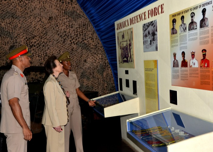 Her Royal Highness, the Princess Royal, Princess Anne, is given a history of the Jamaica Defence Force (JDF) by Curator of the Military Museum, Stacey Duhaney (right), while Chief of Defence Staff, Major General Antony Anderson, looks on. Her Royal Highness toured Up Park Camp on October 1, as part of her three-day visit to the island from September 30 to October 2.