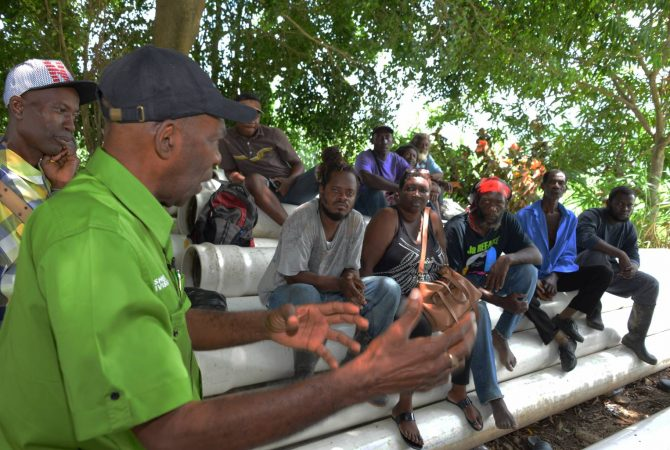 Minister without Portfolio in the Ministry of Industry, Commerce, Agriculture and Fisheries, Hon. J.C Hutchinson (left) addresses farmers during a tour of the Plantain Garden River agro-park in St. Thomas on June 24. The Minister told them that the Government would help them recover from the losses as a result of the recent heavy rains.