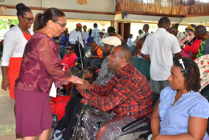 Minister of Labour and Social Security, Shahine Robinson, greets members of the disabled community before the start of the national service for Disabilities Awareness Week at Grace Baptist Church in May Pen, Clarendon. In the background is Executive Director of the Jamaica Council for Persons with Disabilities, Christine Hendricks.