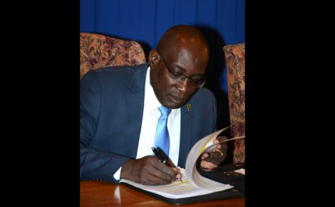 Minister of Education, Youth and Information, Senator the Hon. Ruel Reid, reads over his notes prior to the start of Tuesday's (March 22) Post-Cabinet press briefing at the Office of Prime Minister in Kingston.