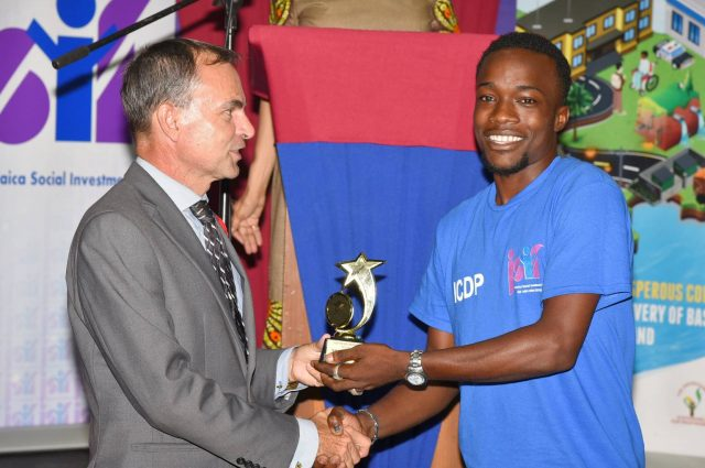 National Coordinator of the Housing, Opportunities, Production and Employment (HOPE) Programme, Lieutenant Colonel Martin Rickman (left) presents Nickoy Davis with a trophy for being the Top Performing Male at the graduation ceremony for participants in the Alternative Livelihood Skills Development programme held at the Chinese Benevolent Association of Jamaica on Old Hope Road on Thursday (October 26). The training programme is a component of JSIF's US$42 million Integrated Community Development Project (ICDP).
