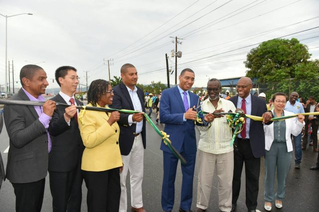 Prime Minister, the Most Hon. Andrew Holness (centre), cuts the ribbon to officially open the newly upgraded 2.44-kilometre section of Marcus Garvey Drive, between East Avenue and Harbour Street in Kingston, on Thursday, October 5. The US$20.5 million project was implemented by the Ministry of Economic Growth and Job Creation through the National Works Agency (NWA) and executed by China Harbour Engineering Company Limited (CHEC) under the Government's Major Infrastructure Development Programme. Sharing in the occasion (from left) are Kingston's Mayor, Senator Councillor Delroy Williams; Ambassador of the People's Republic of China to Jamaica, His Excellency Niu Qingbao; Permanent Secretary in the Office of the Prime Minister/Ministry of Economic Growth and Job Creation, Audrey Sewell; Opposition Spokesman on Works, Mikael Phillips; Local Government and Community Development Minister and Member of Parliament for West Kingston where the roadway is located, Hon. Desmond McKenzie; NWA Chief Executive Officer, E.G. Hunter; CHEC Deputy General Manager, Dr. Zhimin Hu; and NWA Communication and Customer Services Manager, Stephen Shaw.