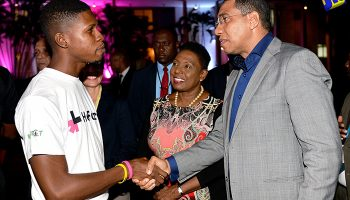 Prime Minister, the Most Hon. Andrew Holness (right), is greeted by a Respect Jamaica Youth Ambassador, Mr. Demoy Barrows (left), at the launch of a gender equality campaign - HeForShe Jamaica - at Jamaica House on July 27. Also pictured is Minister of Foreign Affairs and Foreign Trade, Hon. Kamina Johnson Smith (second left, partially hidden); and Minister of Culture, Gender, Entertainment and Sport, Hon. Olivia Grange. The UN Women-supported global campaign, HeForShe, is being implemented locally by Digicel Foundation and Respect Jamaica.