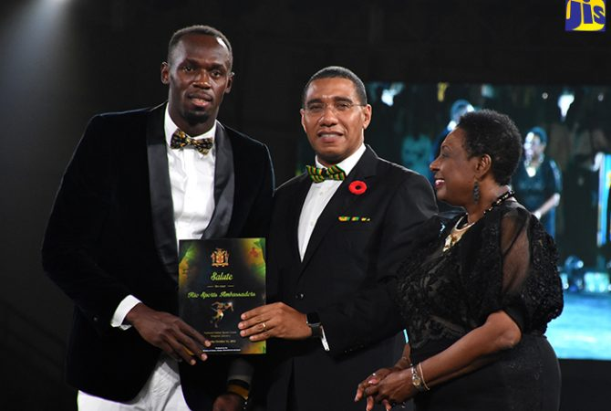 Prime Minister, the Most Hon. Andrew Holness (centre), presents an award to World and Olympic sprint champion, Usain Bolt (left), at a ceremony to honour the 2016 Rio Olympic athletes, at the National Indoor Sports Centre in Kingston, on October 15. Sharing in the moment at (right) is Culture, Gender, Entertainment and Sport Minister, Hon. Olivia Grange.