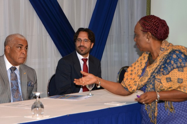 Minister of Water, Land, Environment and Climate Change, Hon. Robert Pickersgill (left), listens to a point being made by National Consultant for  a regional climate change resilience project, Una May Gordon (right), during the opening ceremony for a national workshop on the project, held at the Knutsford Court Hotel in Kingston, today (March 3). Also pictured is Consultant, United Nations Environment Programme (UNEP), Jacinto Buenfil. The US$6 million project, dubbed 'Building climate resilience of urban systems through Ecosystem-based Adaptation (EbA) in Latin America and the Caribbean (LAC)',  seeks to increase the climate change resilience of vulnerable urban communities in three medium-sized LAC cities in Jamaica, Mexico and El Salvador.