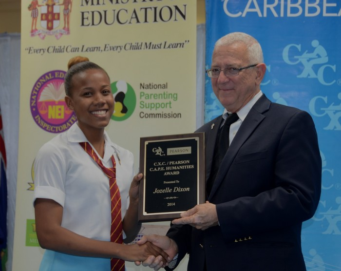 Education Minister, Hon. Rev. Ronald Thwaites (right), presents Wolmer's Girls' School student, Jozelle Dixon, with her award for being adjudged the Most Outstanding Candidate in Humanities in the 2014 Caribbean Examinations Council (CXC) Caribbean Advanced Proficiency Examinations (CAPE), during the presentation ceremony at the University of the West Indies (UWI)  Regional Headquarters, Mona, St. Andrew. Jozelle was also awarded the CXC/Pearson Humanities Award, for distinction and credit grades earned in eight CAPE units.