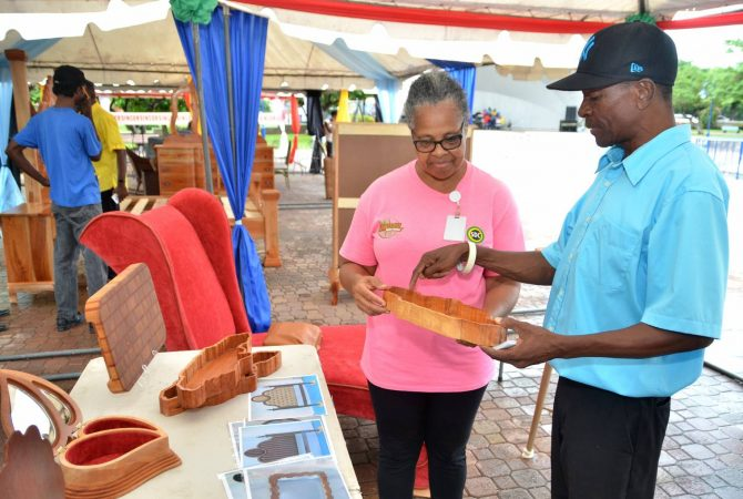Owner of Furniture Anomaly, Richard Weise, points out features of a decorative wood item to Social Development Commission (SDC) Parish Manager for Kingston and St. Andrew, Sandra Goulbourne. Occasion was the SDC's Home and Furnishing Expo held recently at Emancipation Park in St. Andrew.