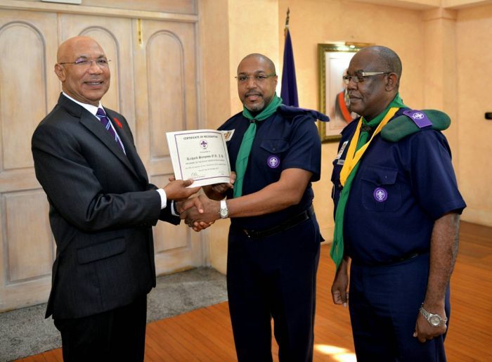 Governor-General, His Excellency the Most Hon. Sir Patrick Allen (left), presents new President of the Scout Association of Jamaica, Richard Simpson (centre), with a certificate of recognition during the Renewal of Promise ceremony to officially install Mr. Simpson held on Friday (October 6) at King's House. Sharing the moment is Chief Commissioner of the Scout Association of Jamaica, Maurice Brown.