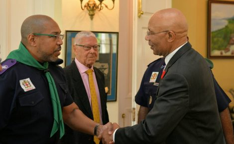 Governor-General, His Excellency the Most Hon. Sir Patrick Allen (right), congratulates the new President of the Scout Association of Jamaica, Richard Simpson, during the Renewal of Promise ceremony to officially install Mr. Simpson held on Friday (October 6) at King's House. Looking on is outgoing President, Dr. the Hon. Oliver Jones who served as President of the Association for 27 years.