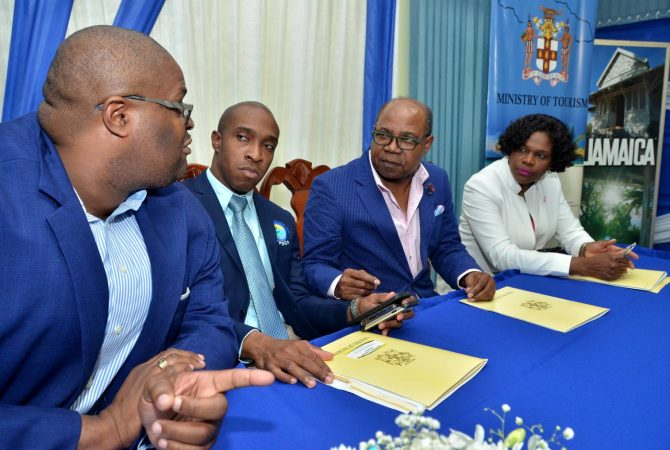 Minister of Tourism, Hon. Edmund Bartlett (second right), listens to Senior Advisor at his Ministry, Dr. Lloyd Waller (left). Occasion was a press briefing on Friday (October 6) at the Jamaica Tourist Board (JTB) offices in New Kingston, where the Minister outlined recovery measures for Caribbean states impacted by recent hurricanes. Others (from second left) are Executive Director of the Tourism Product Development Company (TPDCo), Dr. Andrew Spence; and Permanent Secretary in the Ministry, Jennifer Griffith.