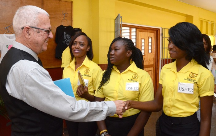 Minister of Education, Hon. Rev. Ronald Thwaites (left), greets students of the Trench Town Polytechnic College, at the official opening of the institution located in South St. Andrew on November 17. The students (from left) are: Sasha Barnes, Tosshell Small and Shushanna McKoy.