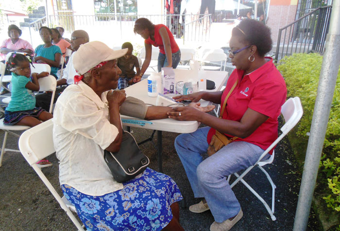 Chief Executive Officer of T's Pharmacy, Judith Townsend (right), checks the blood pressure of a resident of the Darliston community during the pharmacy's annual health fair, held recently.