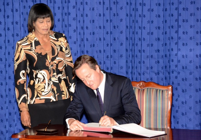 Prime Minister, the Most Hon. Portia Simpson Miller (standing), observes as Prime Minister of the United Kingdom (UK), the Rt. Hon. David Cameron signs the guest book at the Office of the Prime Minister, in Kingston, today (September 29), prior to holding bilateral discussions. Mr. Cameron, who arrived today, is on a two-day official visit.