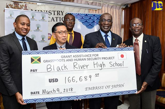 Ambassador of Japan to Jamaica, His Excellency Hiromasa Yamazaki (2nd left), is joined by Minister of Education, Youth & Information, Senator the Hon. Ruel Reid (2nd right); and State Minister in the Ministry, Hon. Floyd Green (left), in handing over a cheque for the construction of new classrooms at Black River High School in St. Elizabeth to Chairman of the institution, Vincent Guthrie (right). The presentation was made at the Ministry in Kingston on Friday (March 9). Looking on is Acting Principal of the school, Theobald Fearon.