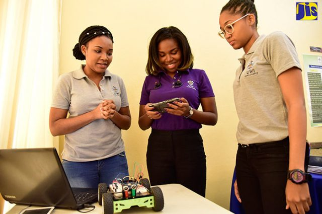 A robotics team from the Mona School of Engineering, University of the West Indies (UWI), demonstrate their innovation during a function hosted by the Gender Committee for the Offices of the Prime Minister and the Cabinet at Jamaica House on Friday (March 9). From left are: Sasha-Lee Lewis; Zoe Saunders; and Stefany Hanson.