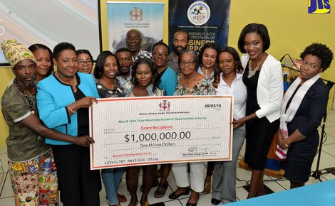 Minister of Culture, Gender, Entertainment and Sport, the Hon. Olivia Grange (2nd left) and entrepreneurs operating within the Blue and John Crow Mountains World Heritage Site, display a cheque for $1 million, which was presented to them to boost their operations. Twenty entrepreneurs received $50,000 each during a ceremony held on March 9 at the Jamaica Business Development Corporation (JBDC) on Marcus Garvey Drive, St. Andrew.