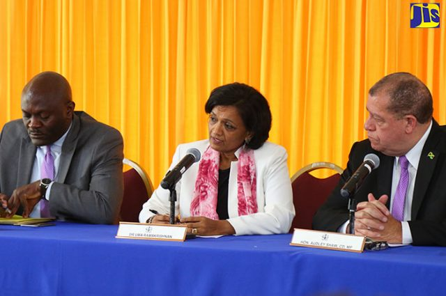 Finance and Public Service Minister, Hon. Audley Shaw (centre), addresses the Government of Jamaica/International Monetary Fund (IMF) press conference at the Office of the Prime Minister on Friday (March 9), where details of the third review under the IMF's Precautionary Stand By Arrangement (PSBA) were announced. Listening (from left) are: Head of the IMF Staff Mission Team which conducted the review, Dr. Uma Ramakrishnan; and Bank of Jamaica Governor, Brian Wynter.