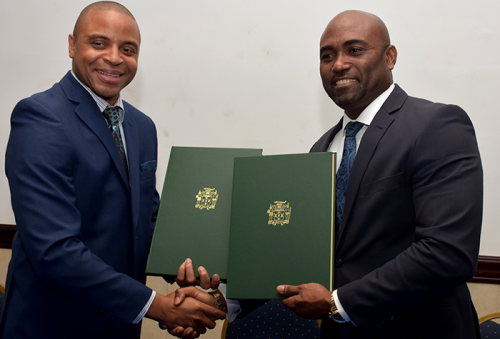Minister of Science, Energy and Technology, Hon. Dr. Andrew Wheatley (right) and Chief Executive Officer of Biojam Industrial Research and Development (BIRD) Global Inc., Christian Strachan, exchange signed copies of a Memorandum of Understanding (MoU) to undertake a feasibility study for the creation of a science and technology park in Jamaica. The signing ceremony was held on July 6 at the Jamaica Pegasus Hotel in New Kingston