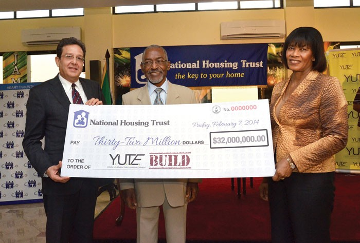 Prime Minister the Most Hon. Portia Simpson Miller (right); along with National Housing Trust (NHT) Chairman, Hon. Easton Douglas (centre); and Chairman, YUTE Limited, Joseph M. Matalon hold aloft a cheque for $32 million that the government, through the NHT, is providing in financial support for phase two of the Youth Employment Through Upliftment (YUTE) Build programme. Occasion was the signing of a Memorandum of Understanding for Phase 2 of the Programme, on February7 at the Office of the Prime Minister.