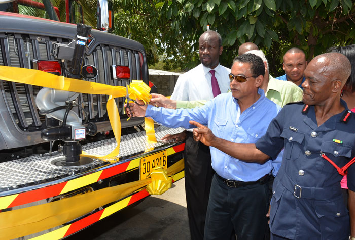 Minister of Local Government and Community Development, Hon. Noel Arscott (centre), cuts ribbon  to officially  hand over new fire truck to Clarendon at the May Pen fire station on July 24. Others  (from left): Mayor of May Pen, Councillor Scean Barnswell (left); Member of Parliament for Central Clarendon, Mr. Mike Henry, and Assistant Commissioner of the Jamaica Fire Brigade, John Forester.