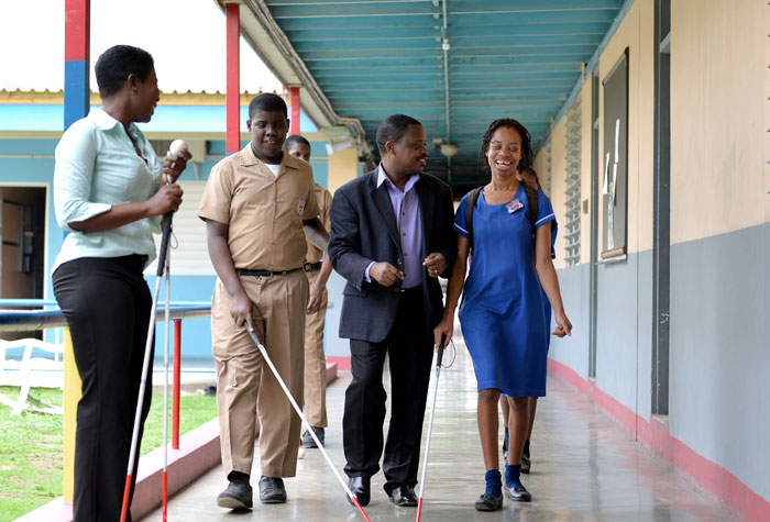 Principal of the Salvation Army School for the Blind and the Visually Impaired, Iyeke Erharuyi (second right), walks  with  students of the school - Sherese Walker (right), and Kimani Nunez (2nd left). Looking on at left is Mobility Instructor, Annette Powell.
