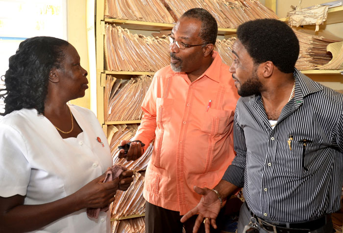 Minister of State with Responsibility for Primary Health Care Infrastructure, Hon. Luther Buchanan (second left), in discussion with Registered Midwife, Central Village Health Centre, Joyce Thomas Robinson (left), when he visited the facility on July 28.  At right is Acting Chairman, South East Regional Health Authority, Dr. Andrei Cooke.