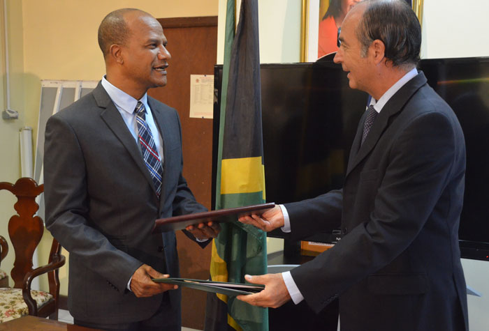 Minister of National Security, Hon. Peter Bunting (left), and Chile's Ambassador to Jamaica, His Excellency Eduardo Bonilla, symbolically exchange documents containing the Defence Technical Agreement, signed on October 21 between both countries, at the Ministry of National Security, Oxford Road, in St. Andrew.
