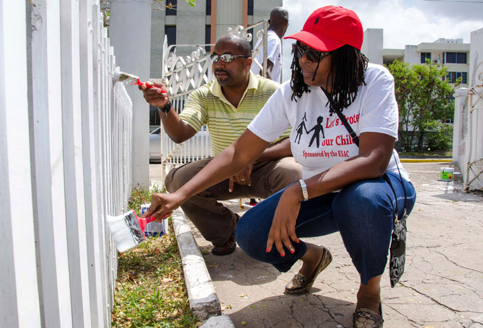 Mayor of Kingston and St. Andrew, Senator Dr. Angela Brown Burke (right), and Minister of State in the Ministry of Science, Technology, Energy and Mining and Member of Parliament for South Eastern St. Andrew, Hon. Julian Robison, paint a section of fence at the Jamaica Christian Boys' Home in New Kingston today (May 25). A team of volunteers carried out Labour Day activities at the home, which included the painting of exterior walls, dormitories, bathrooms, and gardening work. Twenty-two mattresses were also donated to the facility.