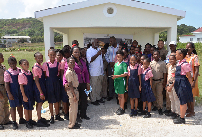 President of the Grand Palladium Staff Association, Leroy Peart (centre) addresses a ceremony to officially open and hand over the newly constructed bus shed at the Ester Primary School on September 30. Mayor of Lucea, Wynter McIntosh, teachers and students of the Esher Primary School and citizens of the area joined in the celebratory occasion.
