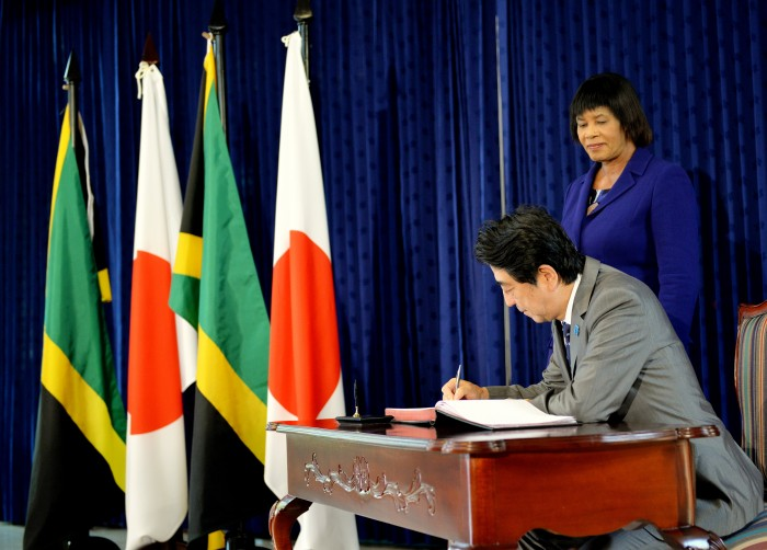 Prime Minister of Japan, His Excellency, Mr. Shinzo Abe signs the guest book at the Office of the Prime Minister in St. Andrew on September 30. Prime Minister, the Most Hon. Portia Simpson Miller, looks on. The Prime Minister held bilateral talks with Mrs. Simpson Miller.