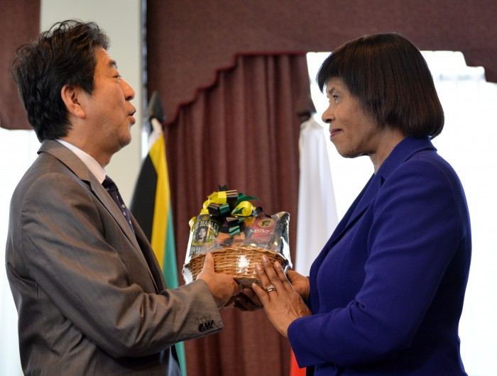 Prime Minister, the Most Hon Portia Simpson Miller presents Prime Minister of Japan, His Excellency, Mr. Shinzo Abe with a gift at the Office of the Prime Minister in St. Andrew, on September 30.