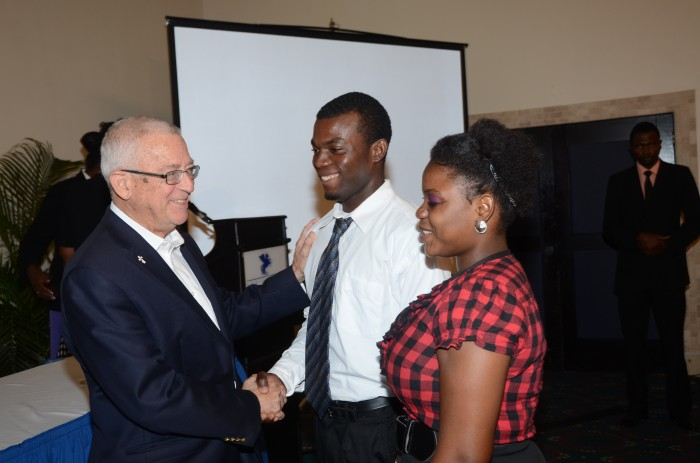 Minister of Education, Hon. Rev. Ronald Thwaites (left), congratulates scholarship awardees, and students on the Career Advancement Programme (CAP), Adrian Stephenson (centre), and Nyoka Taylor (right). They were presented with the scholarships valued over $3 million, by the United States based Union Institute and University, recently at the Jamaica Pegasus Hotel, in New Kingston.