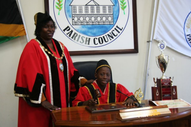 New Youth Mayor for Hanover,  11-year old Clinton Brown (right), is about to strike the gavel to convene his first meeting under the guidance of Mayor of Lucea, Councillor Shernet Haughton (left).  This follows his selection and installation on Monday (November 18), during a ceremony held at the Parish Council chambers in Lucea.