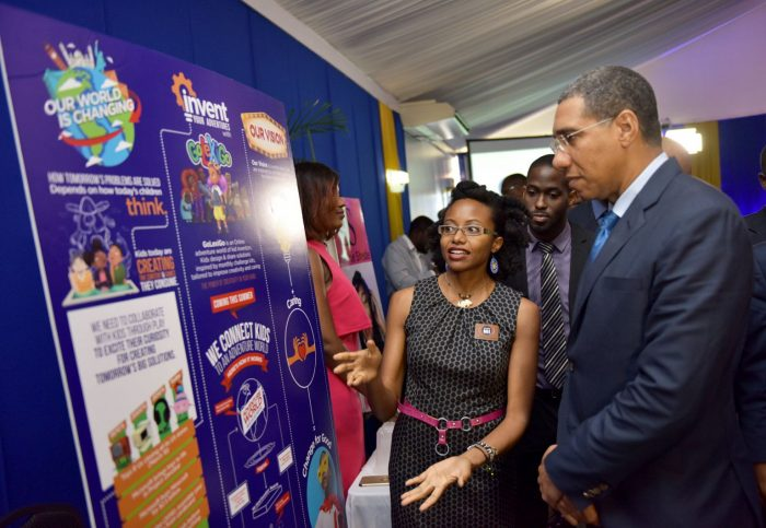 Prime Minister, the Most Hon. Andrew Holness (right), views displays at the booth of business entity, ListenMi Caribbean Limited, being shown to him by Chief Executive Officer, Kenia Mattis (left), during Friday's (April 27) closing ceremony for the Development Bank of Jamaica (DBJ) Innovation Grant from New Ideas to Entrepreneurship (IGNITE). ListenMi Caribbean was one of the 27 entities benefitting from grants and support services under IGNITE's 18-month pilot. Looking on is DBJ's Strategic Services General Manager, Christopher Brown