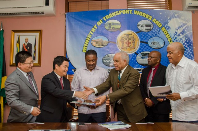 Minister of Transport, Works and Housing, Dr. the Hon.  Omar Davies (4th left), presents Memorandum of Understanding (MOU) to Ambassador of the People's Republic of China in Jamaica, Mr. Xiaojun Dong (2nd left), after signing the document with China Engineering Company (CHEC) for the development of a transshipment hub in the Portland Bight and a feasibility study on the damming of the Bog Walk Gorge, at the Ministry in Kingston, on March 28. Sharing in the occasion are (from left): General Manager of  CHEC, Mr. Zhongdong Tang; Minister of Science, Technology, Energy and Mining, Hon. Phillip Paulwell; Minister with responsibility for Housing, Hon. Dr. Morais Guy, and Minister of Water, Land Environment and Climate Change, Hon. Robert Pickersgill.