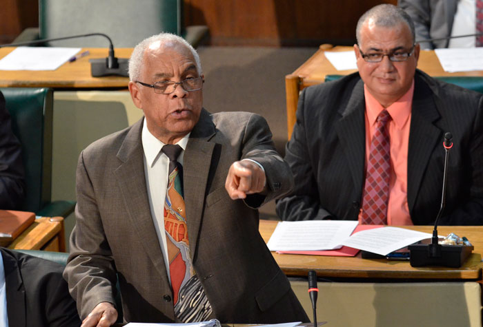 Minister of Transport, Works and Housing, Dr. the Hon. Omar Davies, making his presentation in  the 2014/15 Sectoral Debate in the House of Representatives on  May 14.  Seated at right is  Minister of State in the Ministry of Transport, Works and Housing, Hon. Richard Azan.