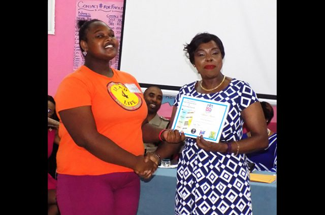 Conceptualizer of the Jamaica Constabulary Force (JCF) IPAD 4 Life Youth Empowerment and Mentorship Camp, Deputy Commissioner of Police (DCP) Novelette Grant (right), presents an award to Tiana McPherson in recognition of her leadership qualities during the just concluded two-week camp at the Spot Valley High School in St. James. The presentation took place during the graduation ceremony for participants in the camp on Friday, July 21.