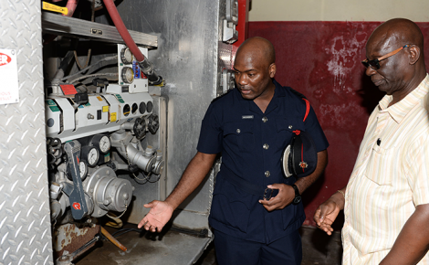 Minister of Local Government and Community Development, Hon. Desmond McKenzie (right), looks on as Superintendent in charge of the Portland division of the Jamaica Fire Brigade, Windell Patterson, points out a compartment in a fire truck used to service the parish. The Minister recently toured local government facilities in the Portland.