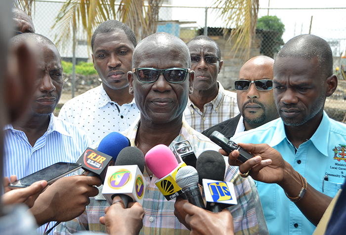 Local Government and Community Development Minister, Hon. Desmond McKenzie (centre), addresses journalists following a tour of flood-affected sections of Marcus Garvey Drive in Kingston on September 16. Also pictured are: National Solid Waste Management Authority (NSWMA) Chief Technical Officer, Audley Gordon (left); Kingston and St. Andrew Corporation (KSAC) City Engineer, Norman Shand (3rd right); KSAC Town Clerk, Robert Hill (2nd right); and Permanent Secretary, Ministry of Local Government and Community Development, Denzil Thorpe.