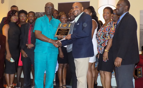 Minister of Local Government and Community Development, Hon. Desmond McKenzie (left foreground) presents a plaque to Chief Executive Officer (CEO) of the Kingston and St. Andrew Municipal Corporation, Robert Hill, in recognition of outstanding performance in property tax collection by the local authority. Occasion was an appreciation luncheon for the all island property tax team, held at the Hilton Rose Hall Resort in Montego Bay, St. James on Friday, July 7. In the background are members of the compliance team.